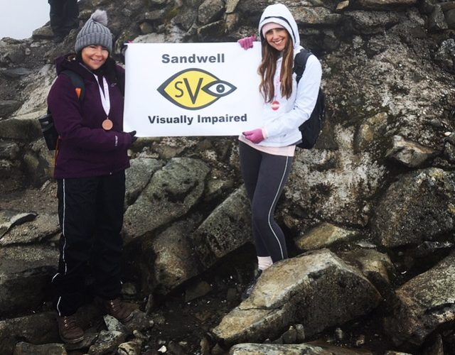 Cassie with an SVI banner at the top of Ben Nevis