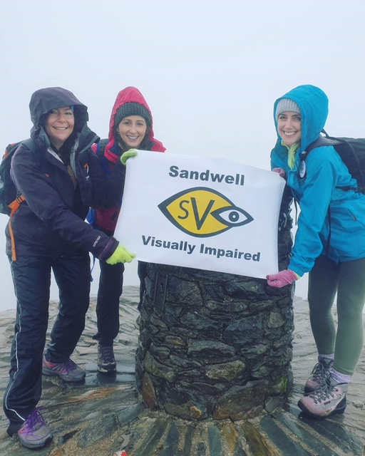 Cassie with friends at summit of Snowden with SVI logo poster