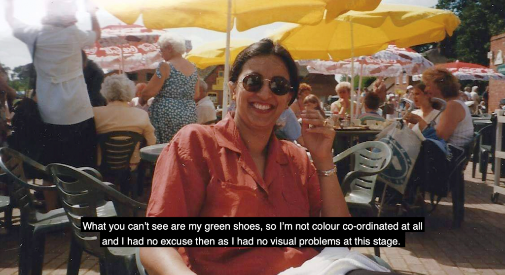 At the centre of this image is an Asian woman in her thirties seated outdoors at a café; she's smiling and wearing sunglasses and a red shirt. Behind her are tables with yellow umbrellas shading groups of people who are socialising on a sunny day.