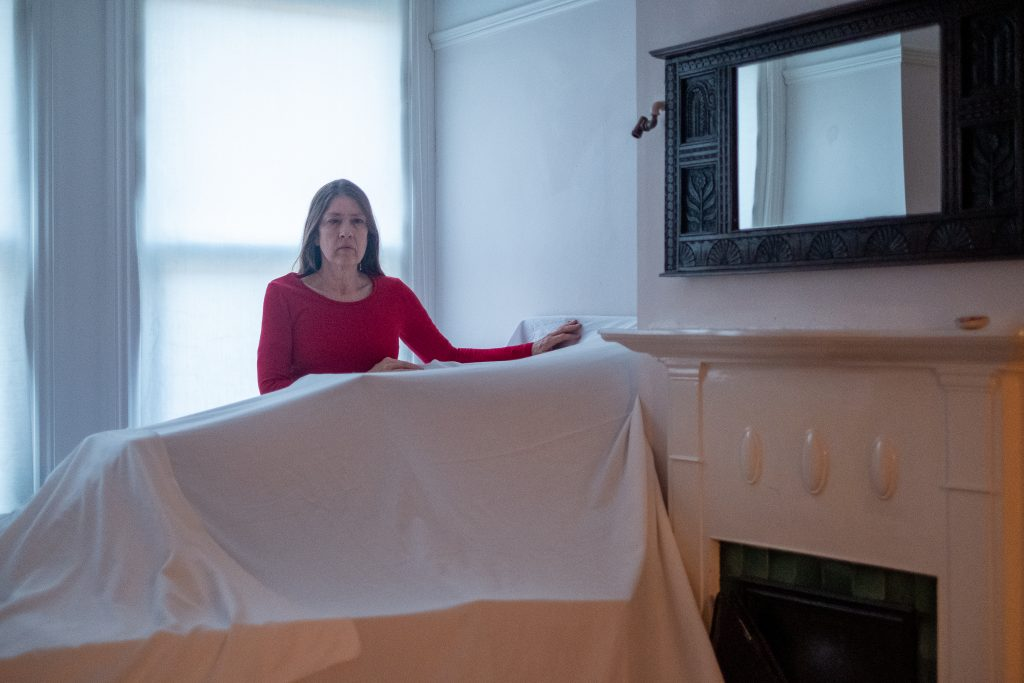 In a bright room a woman in a red top stands behind an item of furniture covered by a white sheet