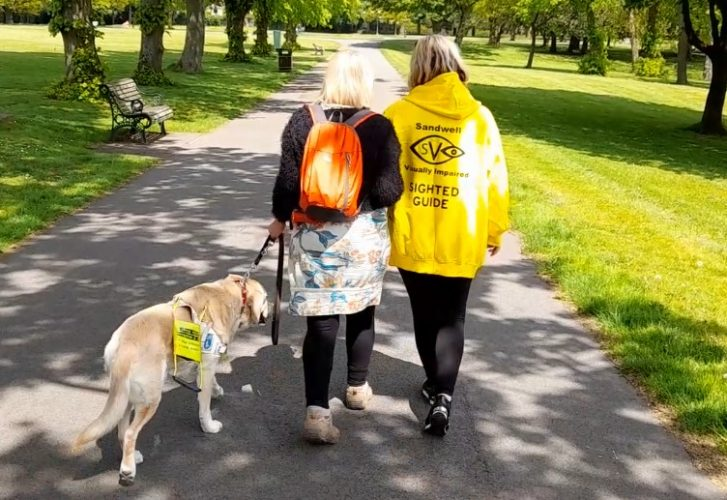 Sighted guide walks with visually impaired woman and guide dog in Dartmouth Park